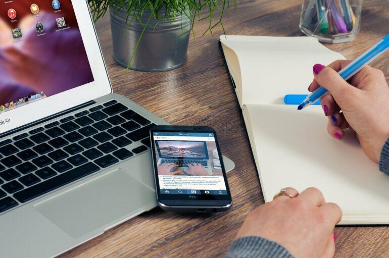Mann vor Laptop mit Handy, Stift und Papier
