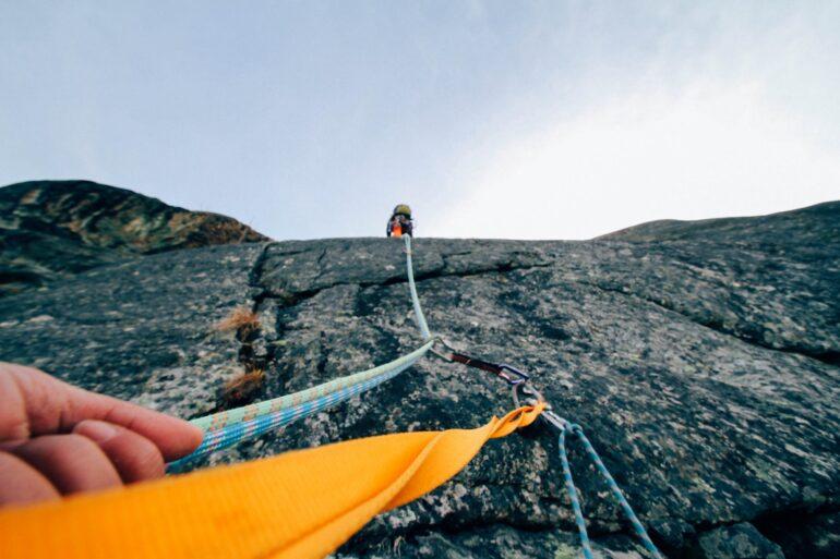 Bild zeigt, wie zwei Menschen eine Felswand hinaufklettern. Voraus geht der moderne Treuhänder/in, der den Unternehmer/in ans Ziel führt.